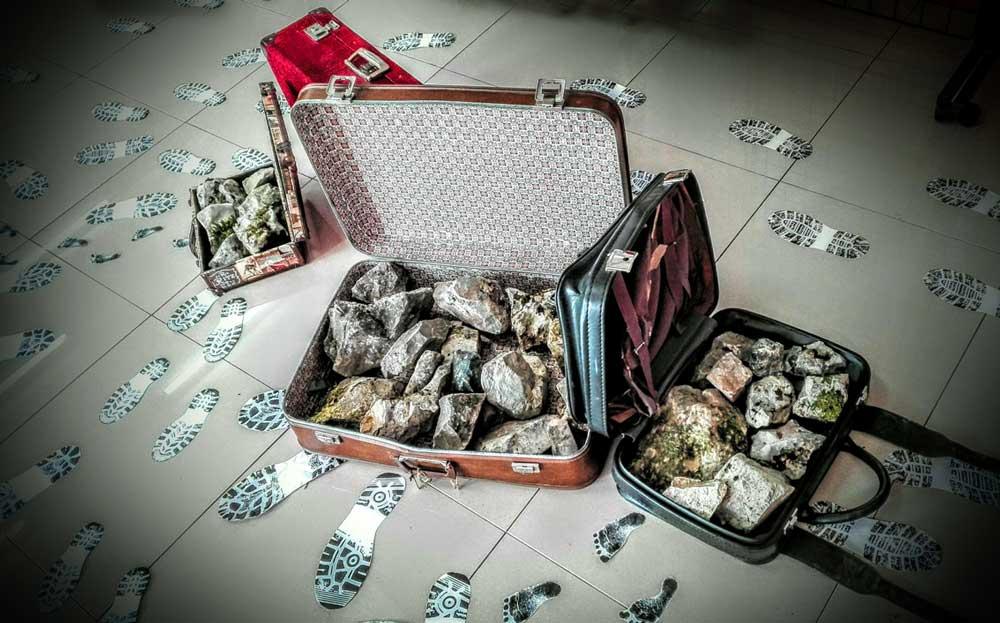 """""""El peso del pasado"""". Instalación objetual con maletas, piedras y huellas, que representa la carga metafórica que deben soportar las personas que han vivido un conflicto."""
